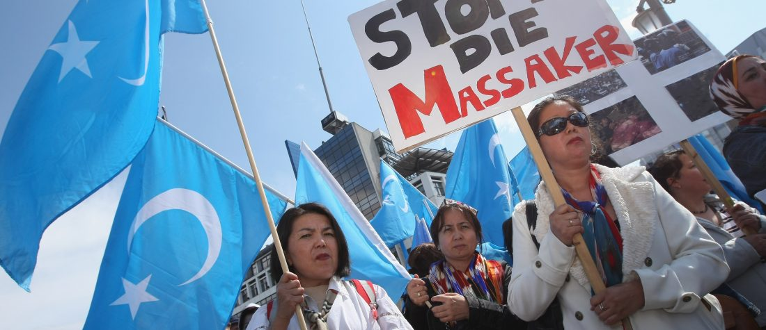 "Uighurs hold East Turkistan flags and a sign that reads ""Stop The Massacres"" near the Chinese embassy in Berlin. Sean Gallup/Getty Images"